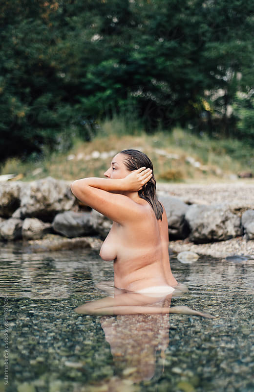 Naked woman standing in sea by Katarina Simovic for Stocksy United