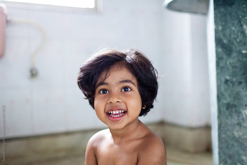 Smiling portrait of a cute little girl in the bathroom by Saptak Ganguly for Stocksy United