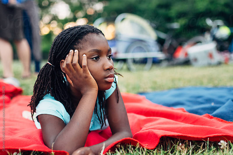 African American girl laying on a blanket in a park by Gabriel (Gabi) Bucataru for Stocksy United