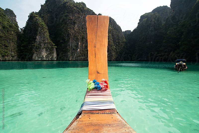 Long tail boat in the sea approaching Ko Phi Phi island by Bisual Studio for Stocksy United