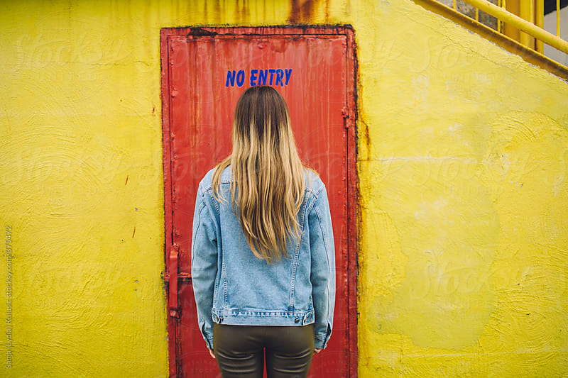 Young woman standing in front of the red door with no entry sign above her by Sanja (Lydia) Kulusic for Stocksy United