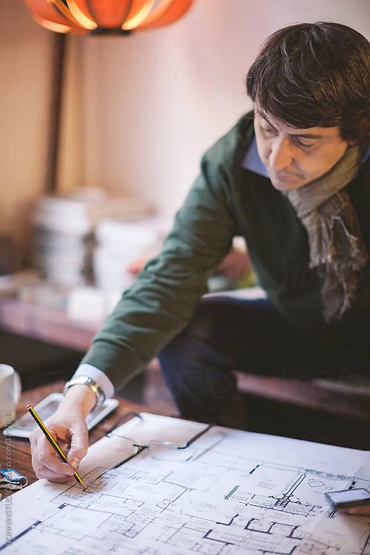 Mature interior designer man working in his studio.  by BONNINSTUDIO for Stocksy United