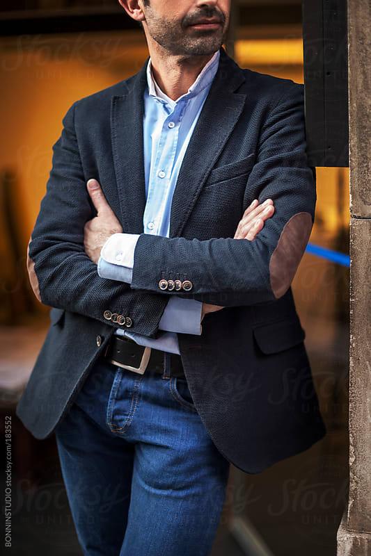 Mature interior designer man with smartphone in front his creative studio. by BONNINSTUDIO for Stocksy United