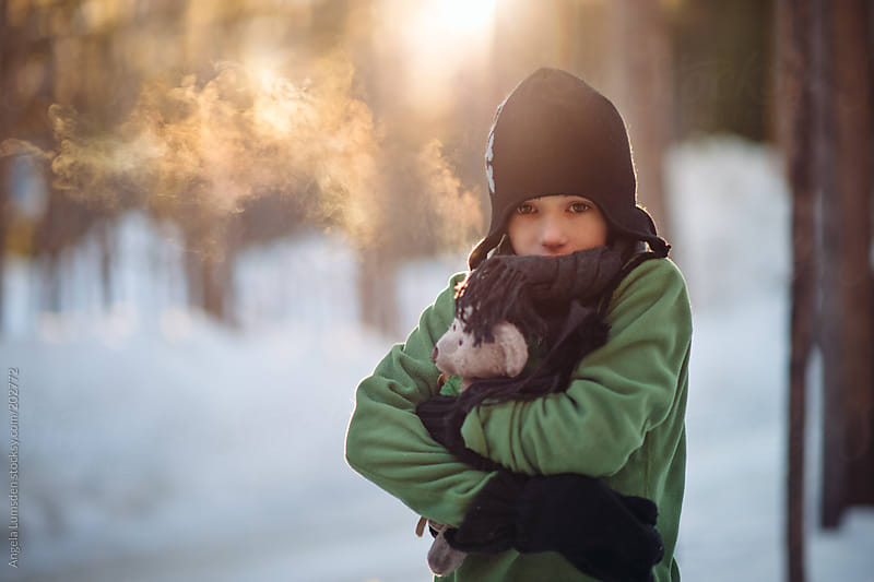 Young boy with his teddy bear outside on a cold morning by Angela Lumsden for Stocksy United