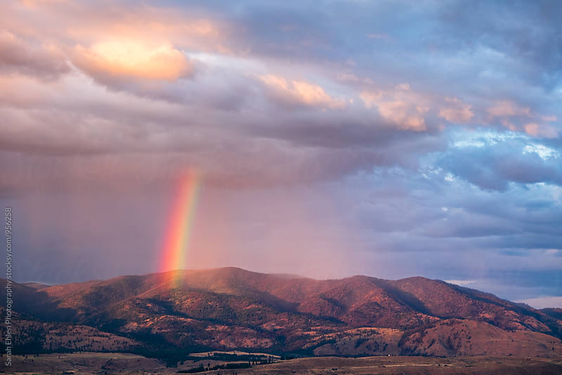 Scenic view of a rainbow and passing storm over a mountain valley by Sarah Ehlen Photography for Stocksy United