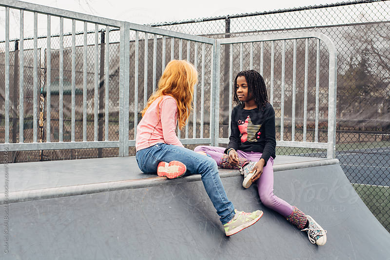Caucasian and black girl chatting on a skate park ramp by Gabriel (Gabi) Bucataru for Stocksy United