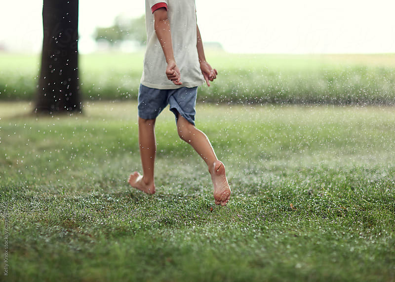 boy runs barefoot through wet grass by Kelly Knox for Stocksy United