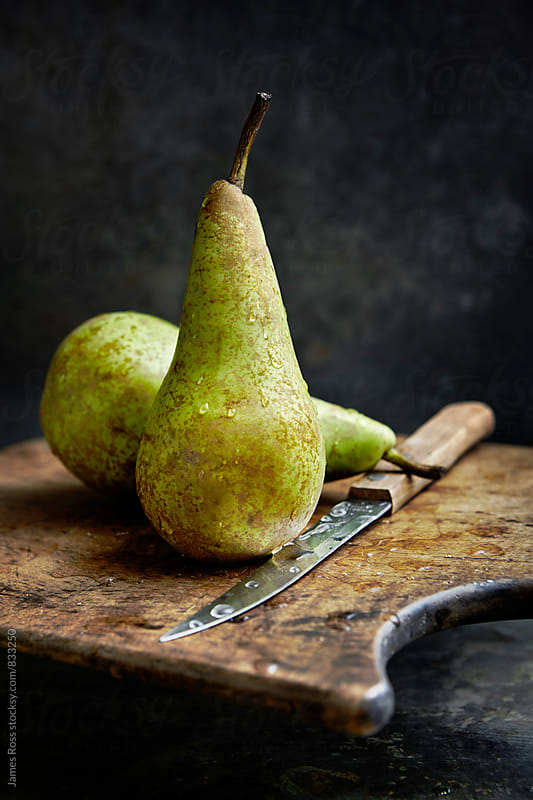 Two pears on a wooden chopping board by James Ross for Stocksy United