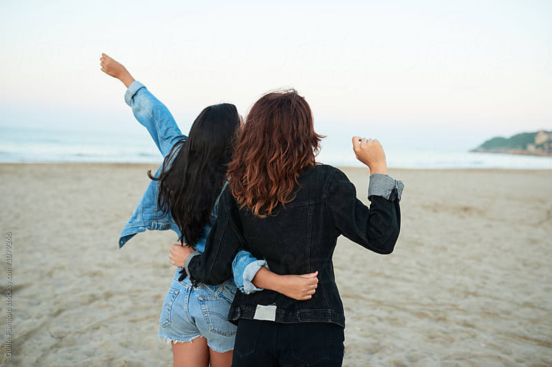 Black-haired and brunette friends on beach by Guille Faingold for Stocksy United