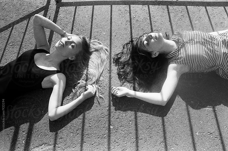 A black and white film portrait of two beautiful young woman lying on the ground by Anna Malgina for Stocksy United