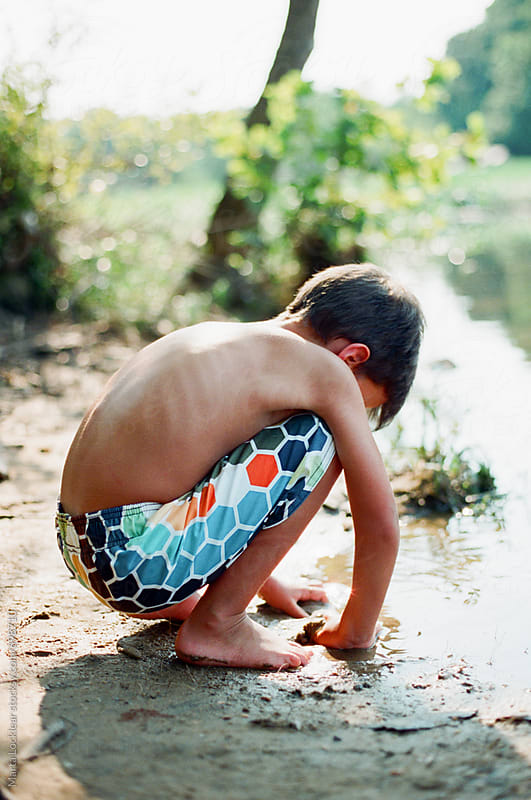 Little boy squatting and playing in the river sand by Marta Locklear for Stocksy United