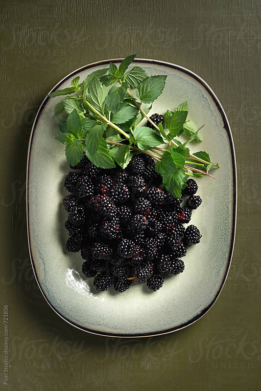 Ripe blackberries and sprigs of mint in plate  by Pixel Stories for Stocksy United