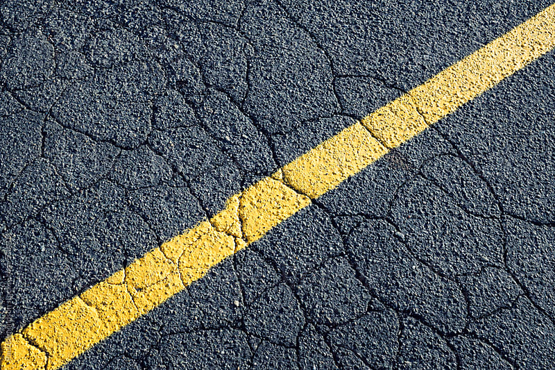 Painted yellow stripe on urban street, close up by Paul Edmondson for Stocksy United