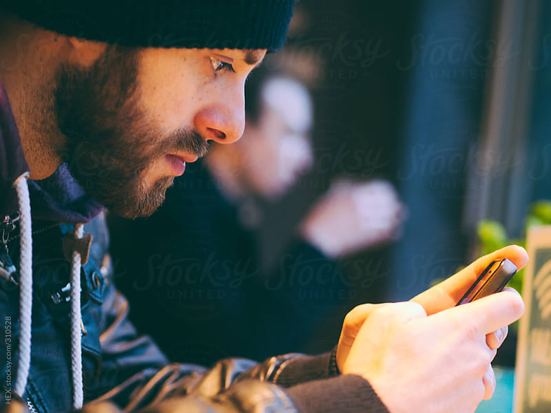 Man Using a Phone in a Coffee Shop . Close up by HEX. for Stocksy United
