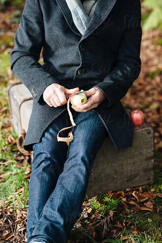 Man peeling an apple outdoors by Suzi Marshall for Stocksy United