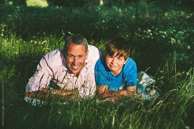 A father and son out doors, smiling. by Helen Rushbrook for Stocksy United