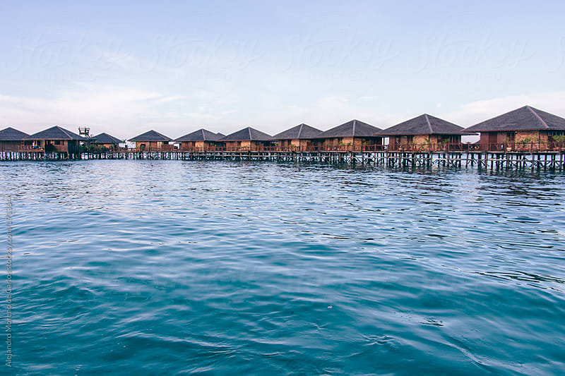 Bungalows - water huts over sea water on resort of tropical island by Alejandro Moreno de Carlos for Stocksy United