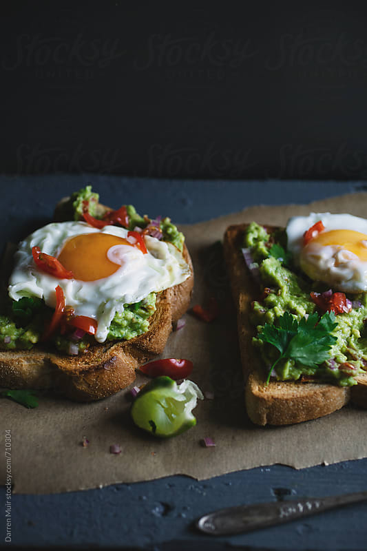 Tasty snack of toast with avocado and fried eggs on table. by Darren Muir for Stocksy United
