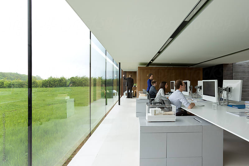 Interior of a glass fronted office with employees working by Paul Phillips for Stocksy United