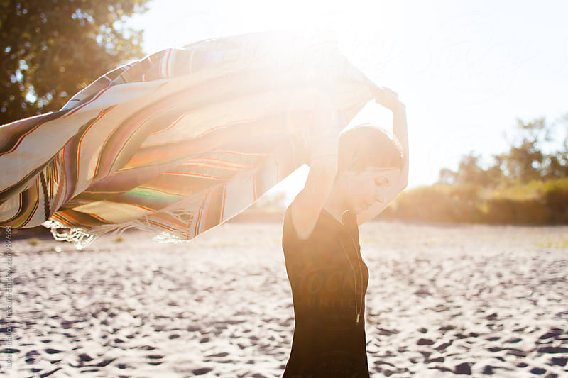 Woman with blanket on beach by luke + mallory leasure for Stocksy United