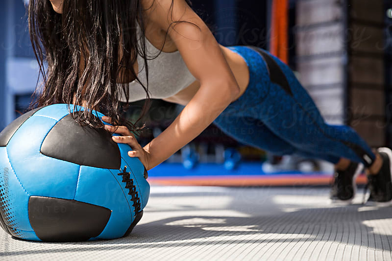 Fit girl doing a push-up with an exercise ball by Jovo Jovanovic for Stocksy United