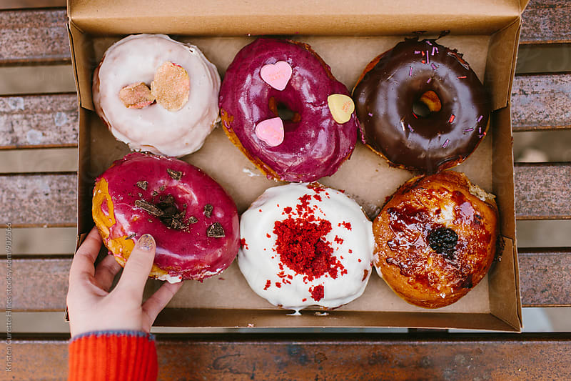 A woman reaching into a box of tasty donuts by Kristen Curette Hines for Stocksy United
