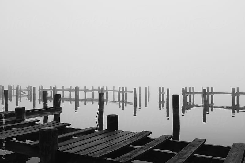 Pier and dock in a river covered by heavy fog and stormy weather in December by Greg Schmigel for Stocksy United