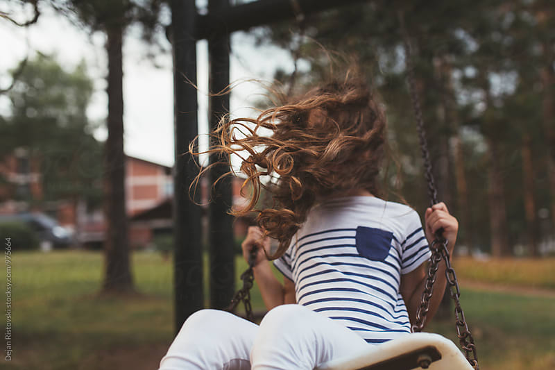 Windy hair of child on swings by Dejan Ristovski for Stocksy United
