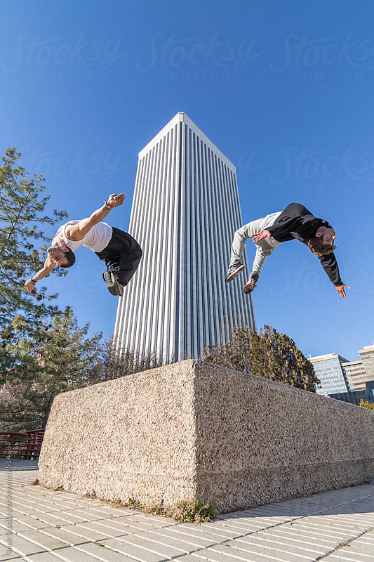 Two men doing a backflip in the air with a building background by Inuk Studio for Stocksy United