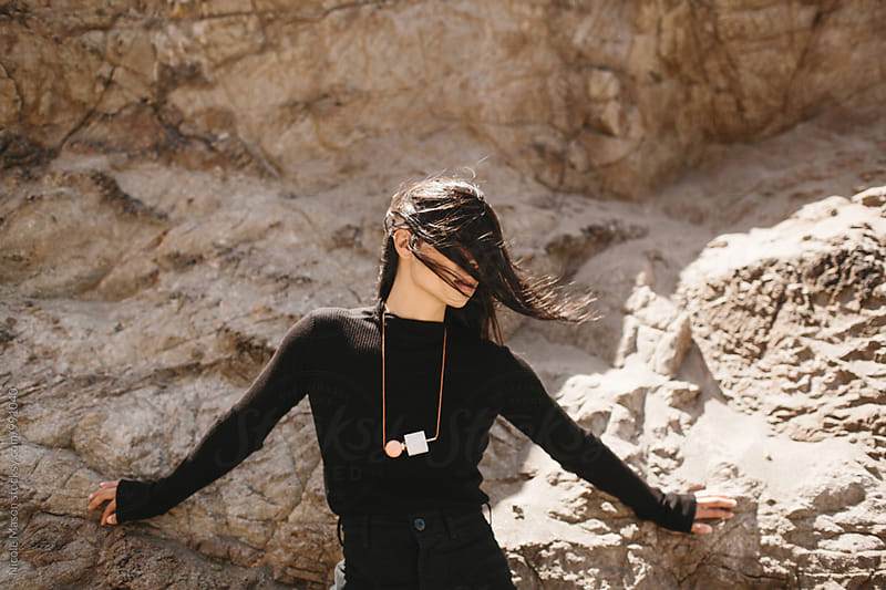 stylish asian woman on rocky coast with hair over face by Nicole Mason for Stocksy United