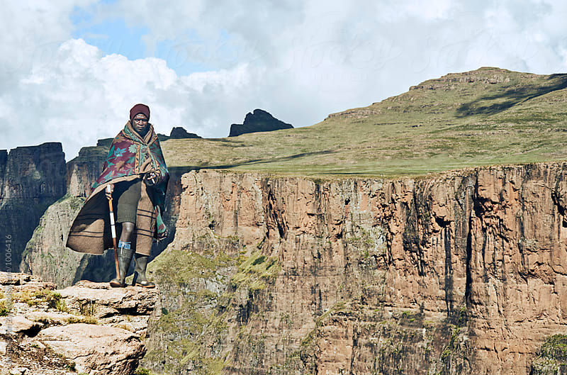 A Basotho shepherd standing on a cliff edge. by Jacques van Zyl for Stocksy United