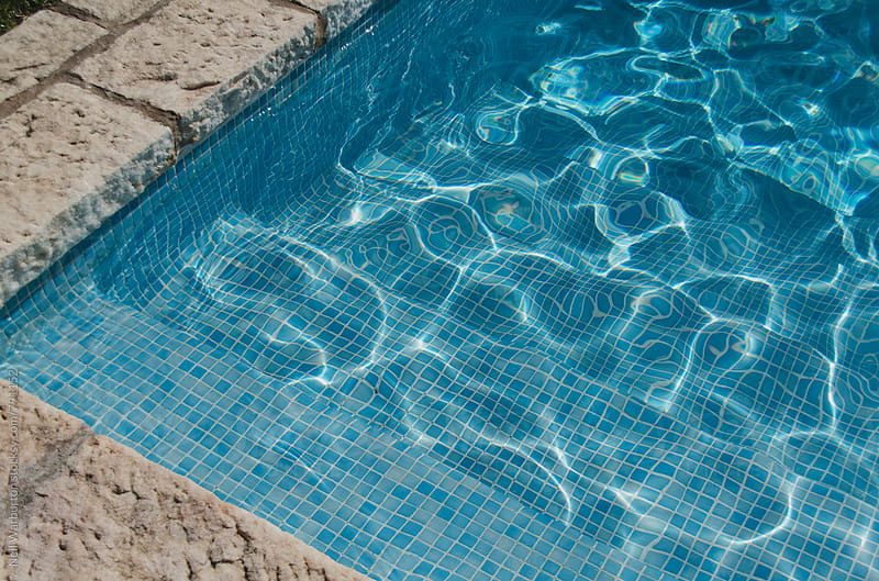 Detail of the corner of a swimming pool with steps by Neil Warburton for Stocksy United
