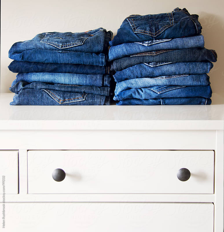 Jeans stacked on a dresser by Helen Rushbrook for Stocksy United