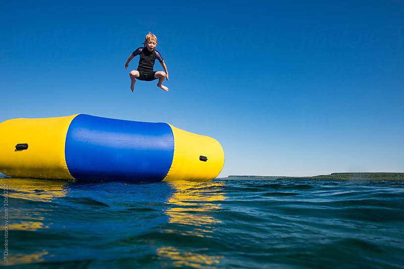 Boy Leaping Into Summer Lake From Water Trampoline At Cottage by JP Danko for Stocksy United