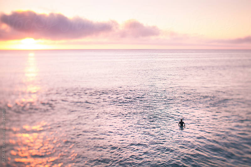 Selective focus (tilt shift) picture of a surfer at sunset. by RZ CREATIVE for Stocksy United