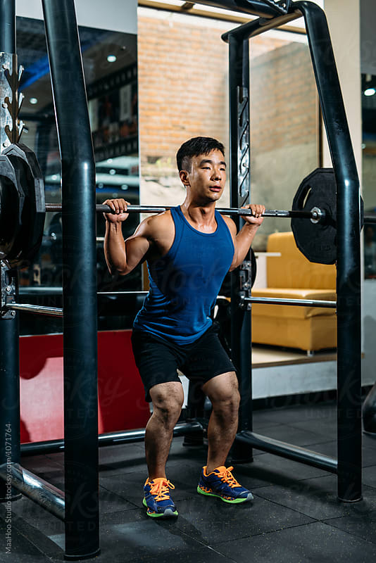 Focused man doing barbell squats at gym by Maa Hoo for Stocksy United
