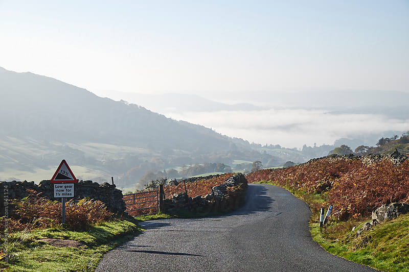 Steep road warning sign and fog in the valley. Cumbria, UK. by Liam Grant for Stocksy United
