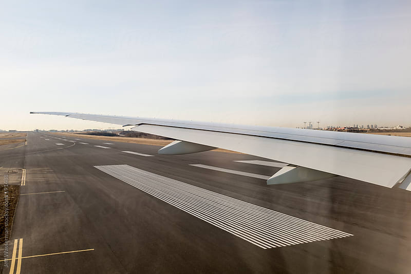 Wing View of Aircraft on Runway by Jeff Wasserman for Stocksy United