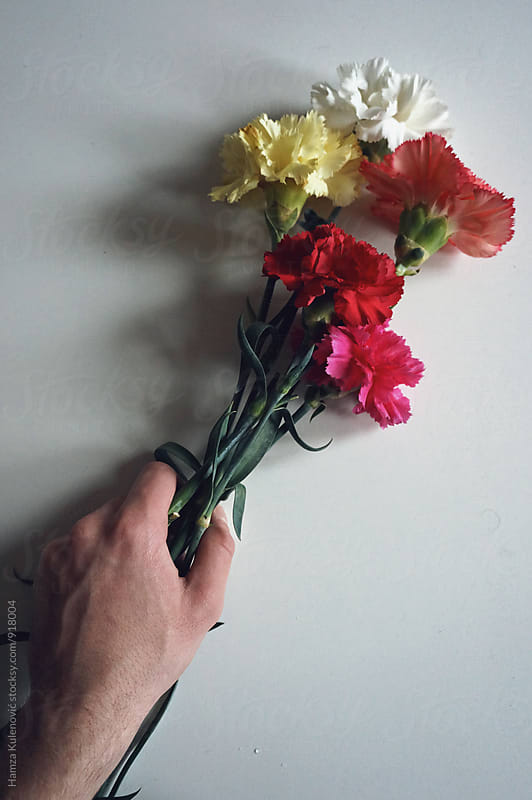 Man holding flowers in his hand by Hamza Kulenović for Stocksy United