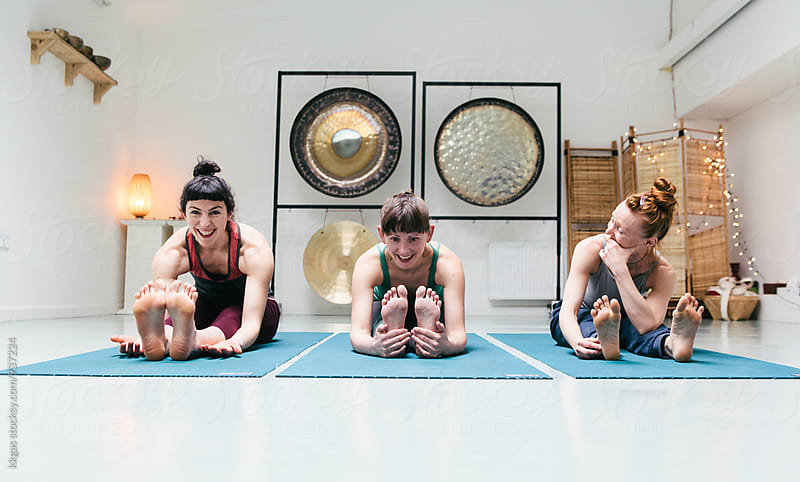 Three women laughing while stretching during a yoga class by kkgas for Stocksy United