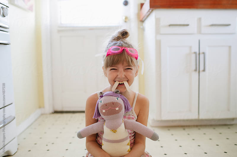 Young girl being silly with hippo doll and goggles by Kristin Rogers Photography for Stocksy United