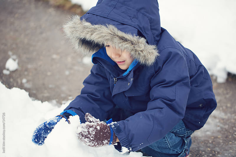 A young child gathers snow for a snowball by kelli kim for Stocksy United