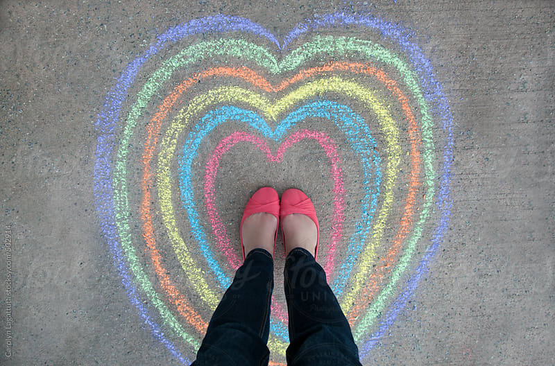 Female standing inside a series of colored chalk hearts by Carolyn Lagattuta for Stocksy United