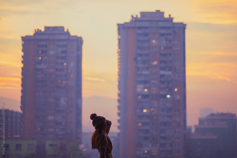 Young beautiful woman with blue eyes and long brown hair outside the city at sunset by Maja Topcagic for Stocksy United