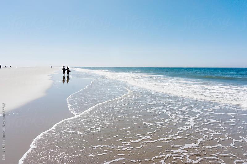 People walking on beach by Robert Kohlhuber for Stocksy United