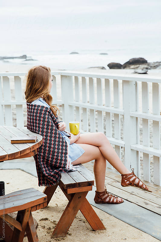 Woman sitting on bench overlooking the ocean by Curtis Kim for Stocksy United