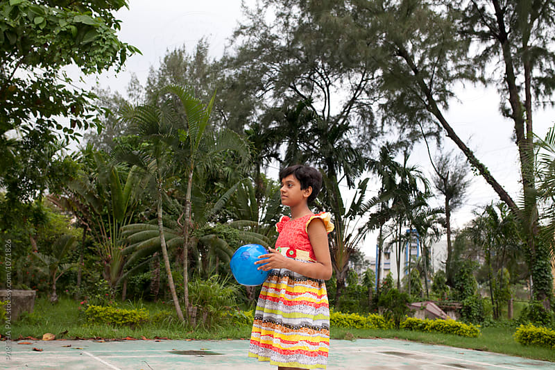 Teenage girl playing with blue colored ball by PARTHA PAL for Stocksy United