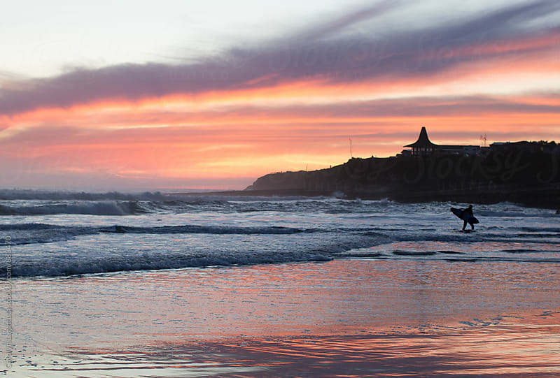Vibrant sunset and surfer coming out of the water by Carolyn Lagattuta for Stocksy United