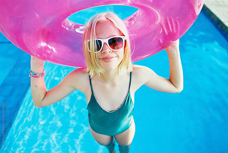 pink floaty with blonde teen girl in white sunglasses wearing a one piece in water wet swimming pool by wendy laurel for Stocksy United