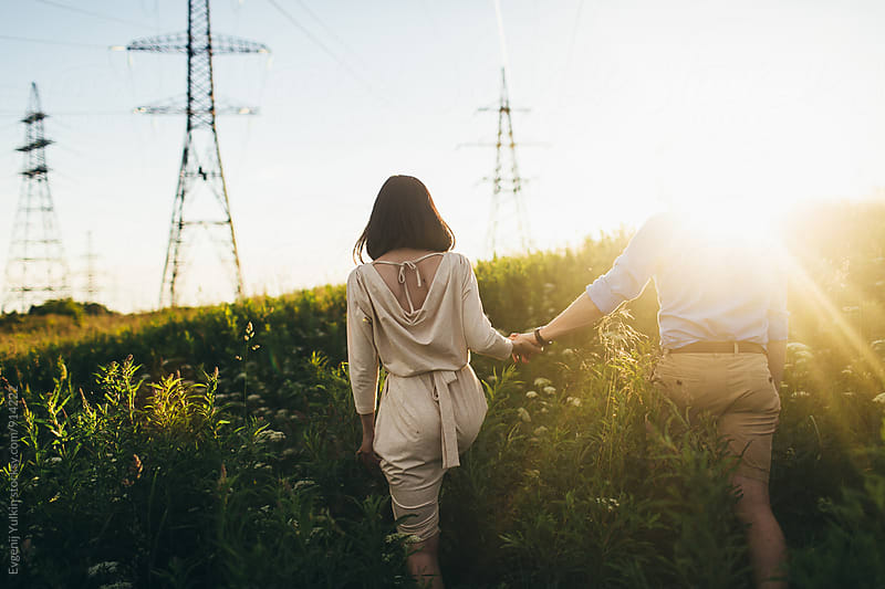 Young couple walking away ander the power lines by Evgenij Yulkin for Stocksy United
